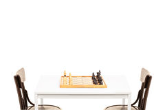 Table with chessboard on it and two wooden chairs Stock Photos
