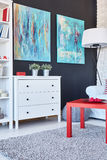 Table, chest of drawers and paintings in a room. Red table, white chest of drawers and blue paintings in a modern room Royalty Free Stock Photo