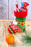 On the table is a Christmas boots with gifts. Royalty Free Stock Images