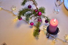 Table with christmas decoration in purple colors. Celebration. A colorful laid table decorated different in purple with xmas decoration for a christmas dinner royalty free stock photo