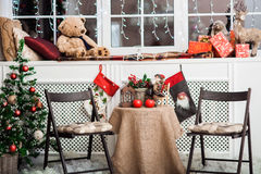 Table with Christmas decoration, stockings, holiday tree, red candle Royalty Free Stock Images