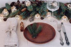 Table with Christmas decorations and garland, ware, green spruce branches. Winter flat lay stock images