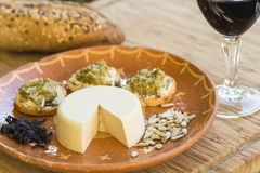Table with vegan cheese and wine. Table with a clay plate with vegan cheese and wine stock images