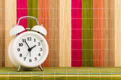 Table clock at coloured decorative background Stock Photos