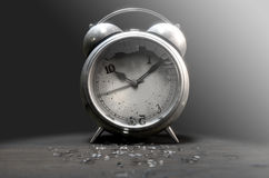 Table Clock Time Run Out. An old worn metal vintage desk clock with a smashed screen and numbers broken off on a dramatic moody dark background - 3D Render Royalty Free Stock Images