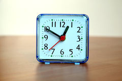 Table clock on wooden table. Table clock square shape showing one o`clock on a table front view closeup Stock Photos