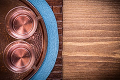 Table cloth coppery tray tea cups on wooden board Stock Image