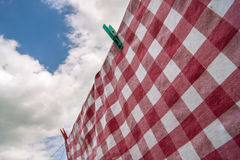 Table cloth hanging to dry. A red checkered table cloth is hanging to dry in de sun, with a blue sky and some clouds in the background Stock Photo