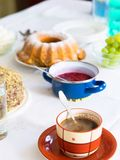 Table with coffe,cake,grape and raspberry sauce. Set table with cup of coffee, marble cake, nut cake, pot with raspberry sauce, bunch of grapes, glass of water Stock Images