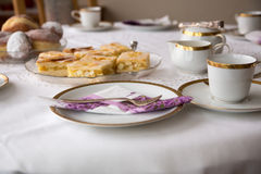 Table with coffe or tea cups, cake, plates Stock Photos