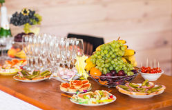 Table with cold snacks and tableware on stand-up party Stock Photo