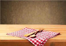 Wooden spoon and fork on checkered napking. Table color red white background nobody view Royalty Free Stock Images