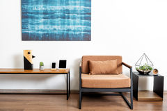 Table with comfy chair and bright picture in shiny apartment Royalty Free Stock Images