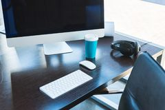 Table with computer, keyboard and cup of coffee. In office Stock Photography