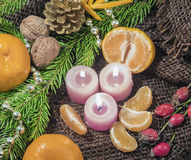 On a table covered with burlap are candles are tangerines, cones, fir or pine twig and berries. Christmas design. On a table covered with burlap are candles are Royalty Free Stock Photo