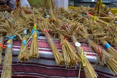 Sheaf of wheat lie on the table. The table is covered with embroidered tablecloth The tablecloth is embroidered with red and black threads Stock Photos