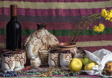 Table covered with ethnic carpet, wine, ceramic jug, glasses, apples Royalty Free Stock Photography