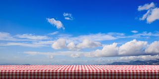 Table covered with red tablecloth on blue sky background, copy space. 3d illustration vector illustration