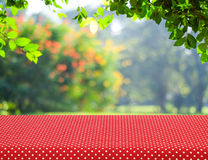Table covered with red polka dot tablecloth over blur trees with Royalty Free Stock Photography