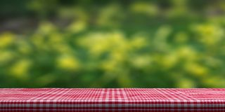 Table covered with red tablecloth on blur nature background, copy space. 3d illustration stock illustration