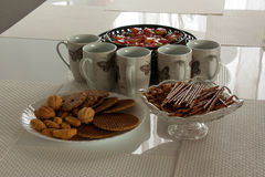 Table covered for the tee. Five cups of tee and three plates with sweets and snack on the white table Stock Photo