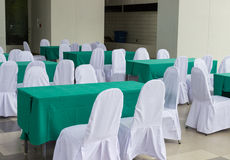 The table covering with green fabric and chair covering with whi Stock Image