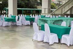 The table covering with green fabric and chair covering with whi Royalty Free Stock Image