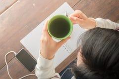 Table créative fonctionnante et boire chaud de thé vert Image stock