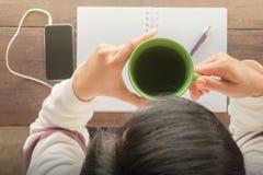 Table créative fonctionnante et boire chaud de thé vert Photo stock