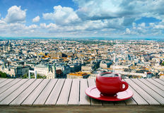 Table with cup of coffee on city background Stock Photos