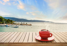 Table with cup of coffee on harbor background Stock Images