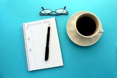 On the table a cup of instant coffee and a pair of glasses stock image