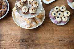 Table with cupcakes, horn pastries, pie and other treats. Copy s Royalty Free Stock Photos