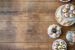 Table with cupcakes, tarts, cake pops and horn pastries. Copy sp Stock Photos
