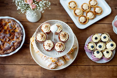 Table with cupcakes, tarts, pie and horn pastries. Stock Photo