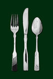 Table cutlery green background. Silver table cutlery or flatware comprising of spoon, knife and fork isolated on a dark green background. Popular symbol for Royalty Free Stock Photos
