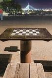 Table d'échecs en parc pendant la nuit, grand pont dans une distance images stock