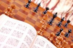 Table d'échecs et livre ouvert Photographie stock libre de droits