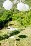 Table d'anneaux de mariage et ballons blancs Photo libre de droits