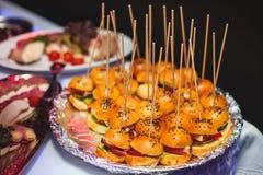 Table de banquet de approvisionnement admirablement décorée avec différents sandwichs à hamburgers d'hamburgers d'un plat sur le  Images libres de droits