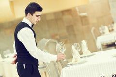 Table de banquet de portion d'homme de serveur au restaurant photographie stock libre de droits