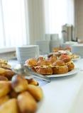 Table de banquet de restauration avec les casse-croûte, les sandwichs, les gâteaux et les plats cuits au four de nourriture Image libre de droits