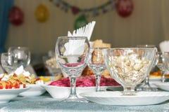 Table de banquet servie avec le fond brouillé Verres de vin vides, salade de légumes et fruit coupé en tranches Vue de côté Photos libres de droits