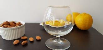 Table de Brown avec le verre de brande, les amandes rôties et les tranches de citrons photo stock