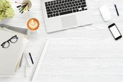 Table de bureau avec l'ordinateur de labtop, le téléphone de magazine vide, les lunettes et la tasse de café intelligents Vue sup Photo stock