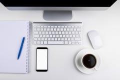 Table de bureau avec l'ordinateur, le clavier d'ordinateur sans fil et la souris, tasse de café, smartphone de comprimé copiez le Photo libre de droits