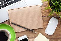 Table de bureau avec l'ordinateur, les approvisionnements, la tasse de café et la fleur Photographie stock libre de droits