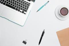 Table de bureau avec l'ordinateur, les approvisionnements, les fleurs et la tasse de café Images libres de droits