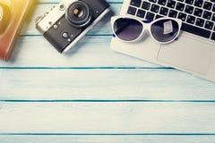 Table de bureau avec l'ordinateur portable et l'appareil-photo Photographie stock libre de droits