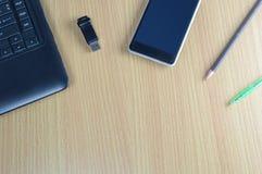 Table de bureau avec l'ordinateur portable et le stylo de smartphone Image libre de droits